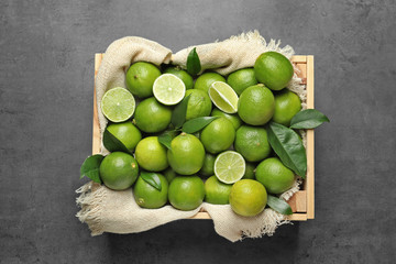 Crate with fresh ripe limes on gray background, top view