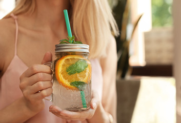 Young woman with mason jar of tasty natural lemonade in cafe, closeup. Detox drink