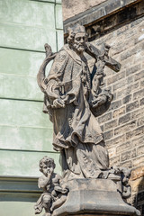 Statue of old priest with cross and Jesus at Old Town in Prague, Czech Republic
