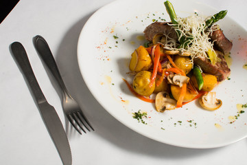 Meat with potato and vegetables on a white table, Fusion Food