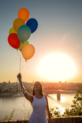 Beautiful young woman holding balloons over a city view while smiling