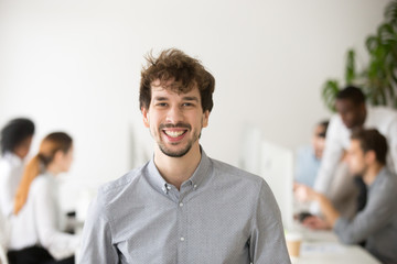 Portrait of smiling male Caucasian employee laughing looking at camera, posing in coworking shared space, shooting for company business catalogue. Concept of laughter, leadership, outsourcing