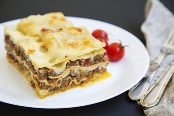 Traditional beef lasagne on a white round plate on black background, side view.