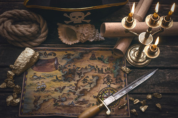 Pirate treasure map, gold nuggets, dagger and pirate hat on aged wooden table background. Sea travel.