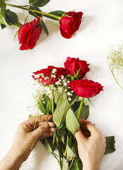Woman making a bouquet of red roses.