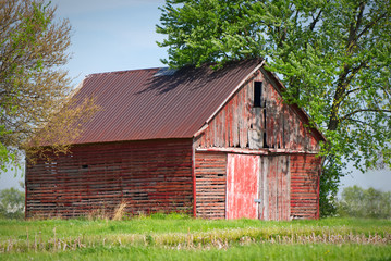 An abandoned farm barn sits in a weathered state as it deteriorate over time