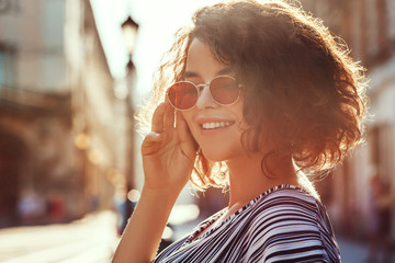 Outdoor close up portrait of young beautiful stylish happy smiling curly girl wearing red narrow oval sunglasses, posing in street. Sunny day light. Summer fashion concept. Copy, empty space for text