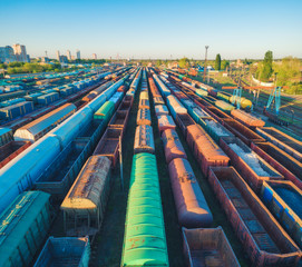 Aerial view of colorful freight trains. Cargo wagons on railway station. Wagons with goods on railroad. Heavy industry. Industrial landscape with train, railway platfform at sunset. Top view. Depot