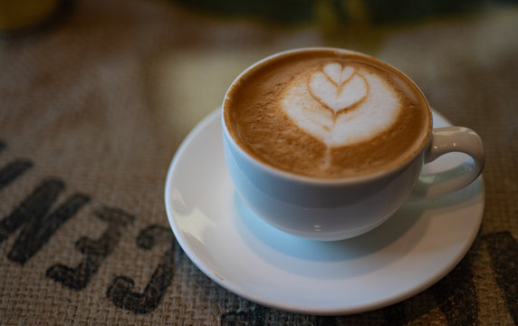 Cup of Cortado coffee on Burlap table.