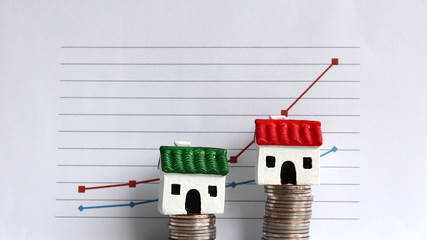 Housingpricerisinganddifferentiatedconcept. A miniature house on a pile of coins in front of a graph.