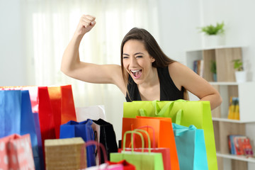 Excited woman looking at multiple shopping bags