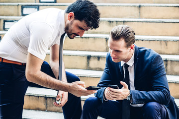 Two business people use technology together of smartphone