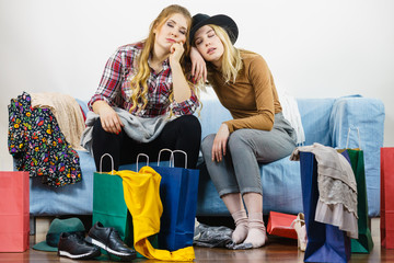 Two bored women next to shopping bags