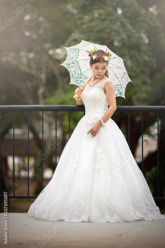 6691a306f65 Young girl in a bridal gown holding a white umbrella on a steel bridge.