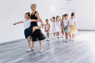 Group of beautiful little girls practicing ballet at dancing class.