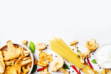 Ingredients for cooking pasta with mushrooms chanterelles in a creamy sauce, food background, top view