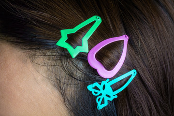 Colored hair clips that are attached to a woman's hair.