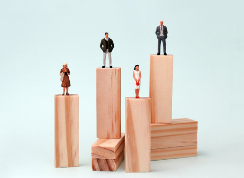 Wooden blocks and miniature people. The concept of the existing promotion gap between men and women.