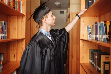 Successful graduate guy, in academic dresses, standing in the library, choosing books, can be used for advertising, text insertion