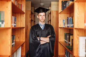 Successful graduate guy, in academic dresses, posing in the library, can be used for advertising, text insertion