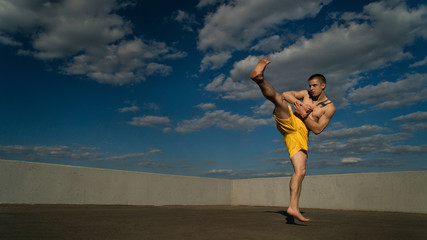 Tricking on street. Martial arts. Man makes roundhouse kick barefoot. Shooted from bottom foreshortening against sky.