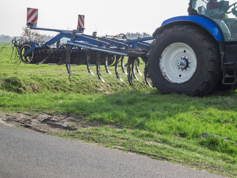 Blue tractor with cultivator
