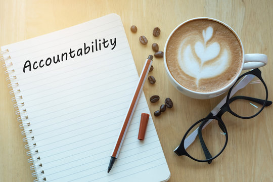 Accountability concept on notebook with glasses, pencil and coffee cup on wooden table. Business concept.