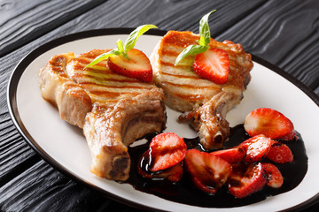 Pork steak fried on a grill and balsamic strawberry sauce close-up on a plate on a table. horizontal