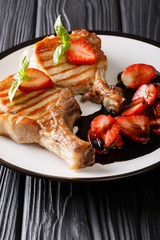 Gourmet grill juicy pork chop served with balsamic strawberry close-up on a plate. vertical