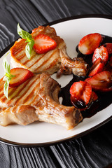 grilled pork chop with a bone served with balsamic strawberry close-up on a plate. vertical