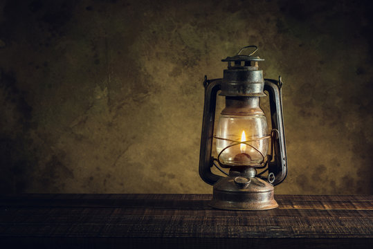 kerosene lamp oil lantern burning with glow soft light on aged wood floor