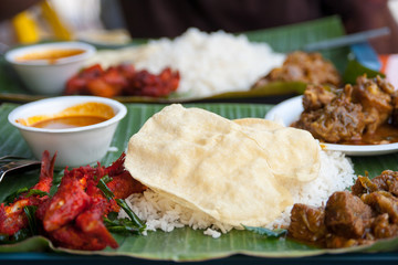 Naan - indian flat bread over steamed rice on banana leaf plate