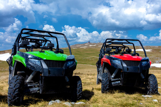 Parked ATV and UTV, buggies on mountain peak with clouds and blue sky in background