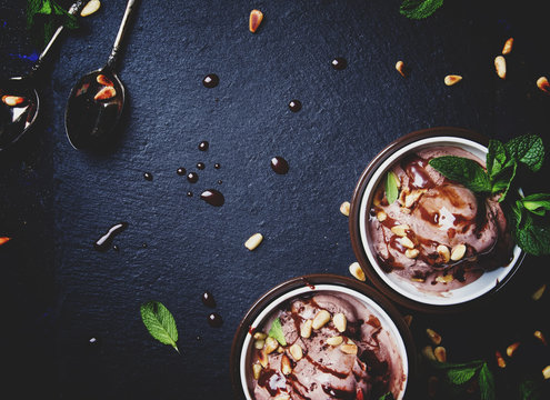 Chocolate ice cream with nuts, dark food background, top view