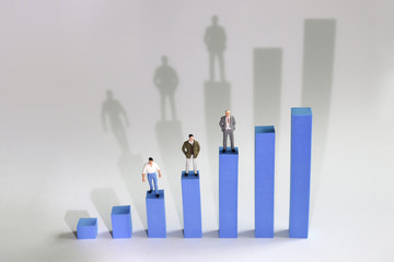 Three miniature men standing on a bar on a blue bar graph. The concept of income gap by occupation type.