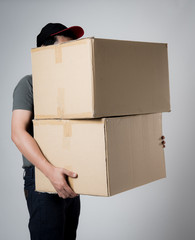 Delivery man holding cardboard boxes on gray background