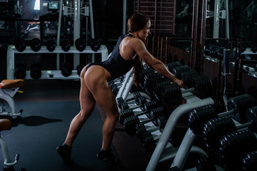 A muscular fitness woman with a very beautiful booty, in a black sexy body, resting and leaning her hands on a row of dumbbells. Dark gym.