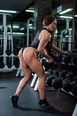 A muscular fitness woman with a very beautiful booty, big muscles, in a black sexy body, resting and leaning her foot on a row of dumbbells. Dark gym.