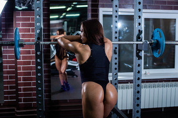 Muscular fitness woman with a very beautiful booty, big muscles, in a black sexy body, resting and leaning on the bar. Dark gym.