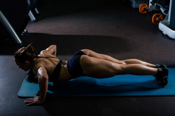 A muscular woman in a black t-shirt and black shorts, performs push-UPS on the floor on a blue rug. Dark gym.
