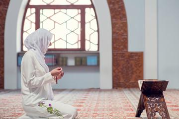 Young beautiful Muslim Woman Praying In Mosque