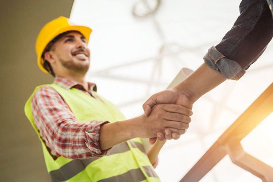 Engineer construction workers in protective helmets and vests are shaking hands while working in the office center
