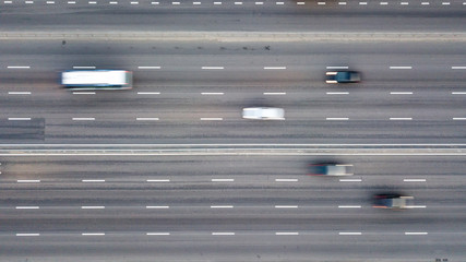 Aerial view from the drone directly above the road to the high-speed highway with high-speed cars.