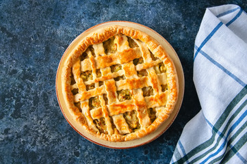 Homemade young cabbage pie from flaky dough  served on a plate. Blue stone background.