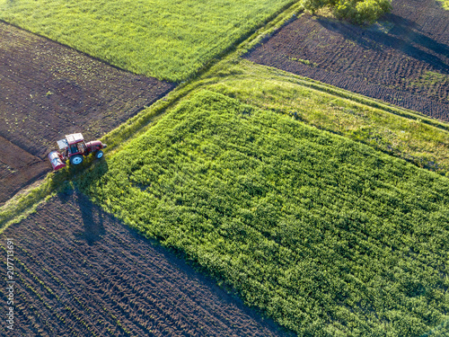 Wall mural Aerial view from the drone, a bird's eye view of agricultural fields with a road through and a tractor on it, in the evening, at sunset