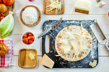 raw homemade traditional italian cheese pizza   on wooden cooking table with ingredients. wallpaper for pizzeria and food concept. top view, flat lay