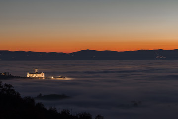 View of St.Francis church (Assisi, Umbria) at dusk, over a sea o