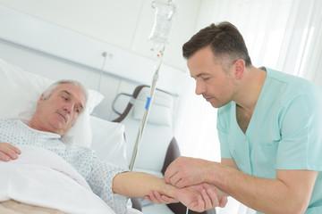 male nurse putting intravenous drip into patients arm