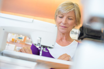 Mature lady using sewing machine