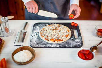 closeup hands of chef making fresh homemade traditional italian pizza. wallpaper for pizzeria and cooking food concept